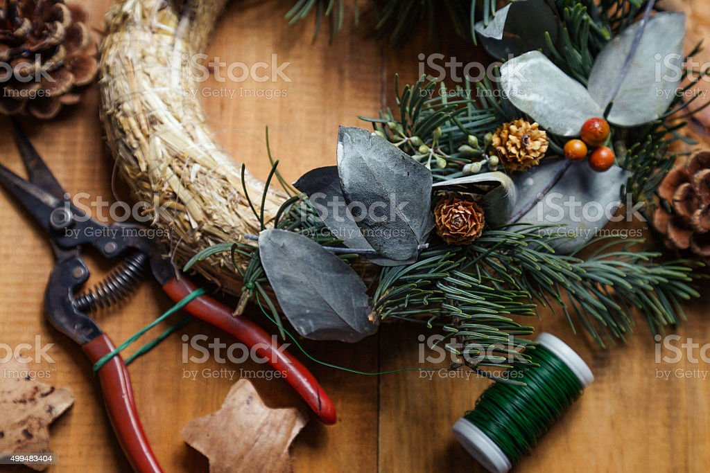 Close up of florist's worktable. Makining of Christmas wreath. stock photo