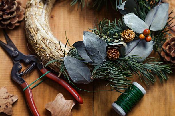 nahaufnahme von einem blumenladen's einen arbeitstisch. makining weihnachten kranz. - diy xmas stock-fotos und bilder