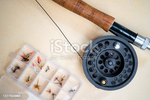 864720746 istock photo Close up of fly fishing rod with reel next to box with tied flies. Fly fishing equipment still life. Nobody 1227503963
