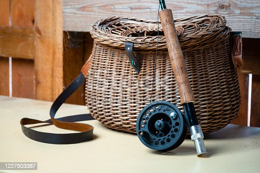864720746 istock photo Close up of fly fishing rod with reel next to braided basket. Fly fishing equipment still life. Nobody 1227503387
