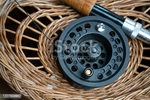 864720746 istock photo Close up of fly fishing rod with reel next to braided basket. Fly fishing equipment still life. Nobody 1227503952