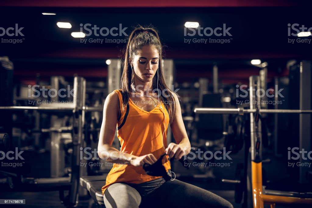 Close up of focused and motivated shape young fitness girl in sportswear sitting on the bench and puts on gloves before exercises in the gym at night. stock photo