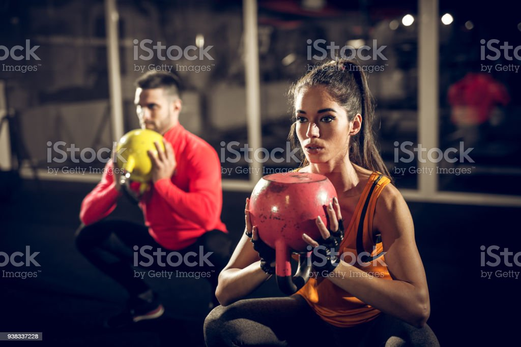 Close up of focused and motivated strong young fitness couple in sportswear crouching with the kettlebells reversed and doing squats in the gym. stock photo