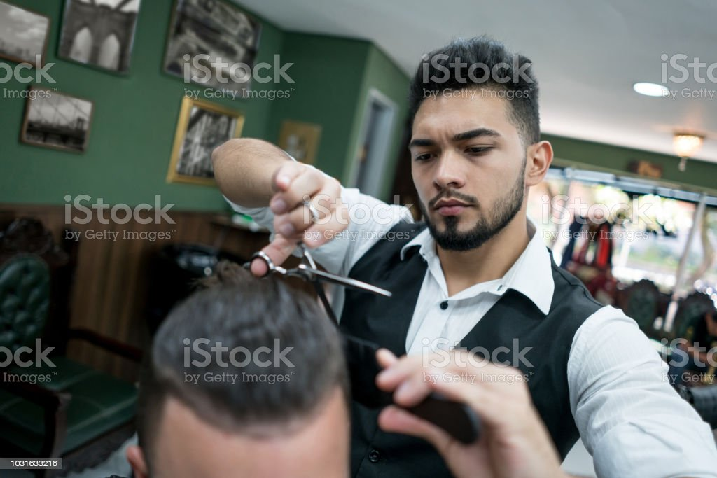 Close up of focused hair stylist cutting a customers hair at a barber...