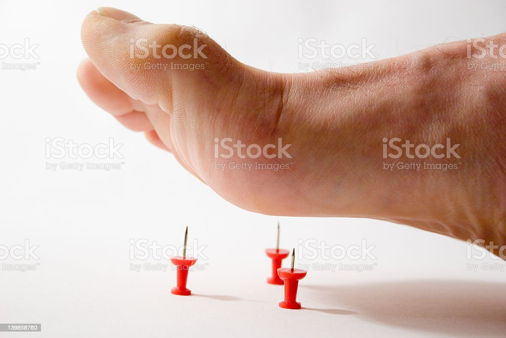 Close up of foot about to step on thumbtacks royalty-free stock photo