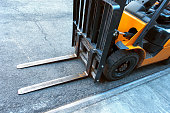 istock close up of fork lift blades on an urban city street 973001328