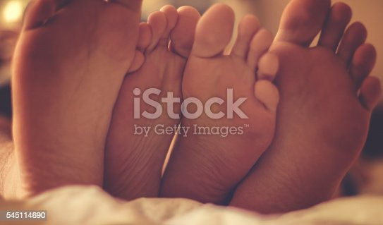 178279911 istock photo Close up of four feet in a bed 545114690