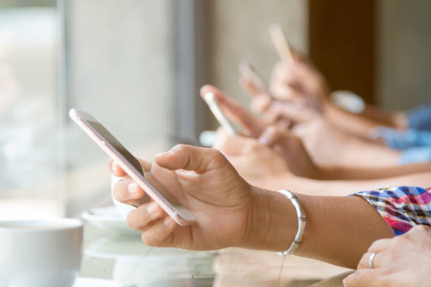 Close up of four people hand holding mobile phone and using internet in coffee shop with warm light flare stock photo