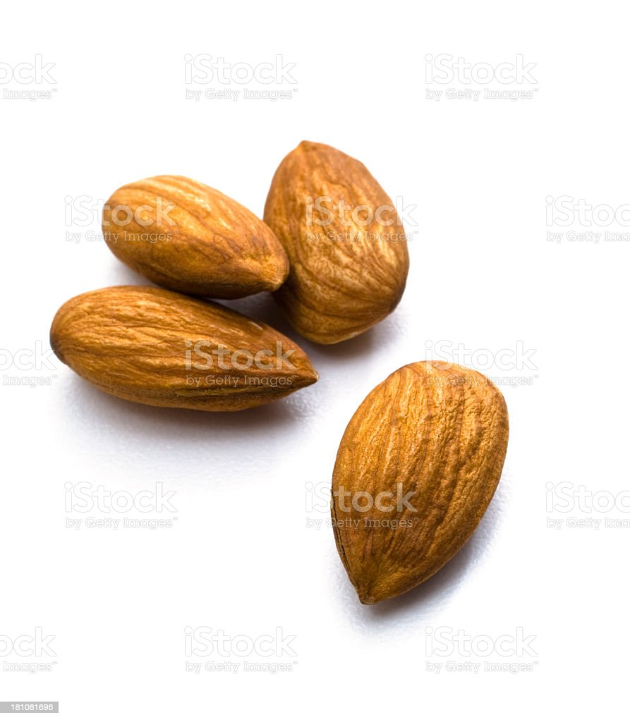 A close up of four whole almonds on a white background royalty-free stock photo