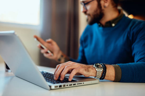 Close up of freelancer typing on laptop and looking at smart phone. stock photo
