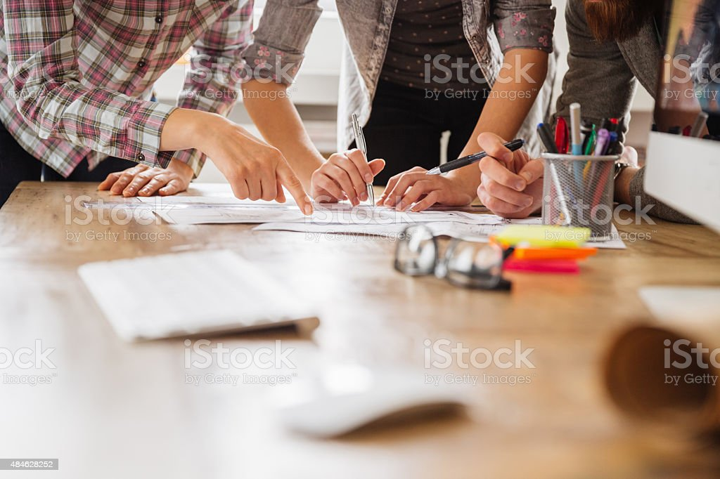 Close up of freelancers hands working by desk stock photo
