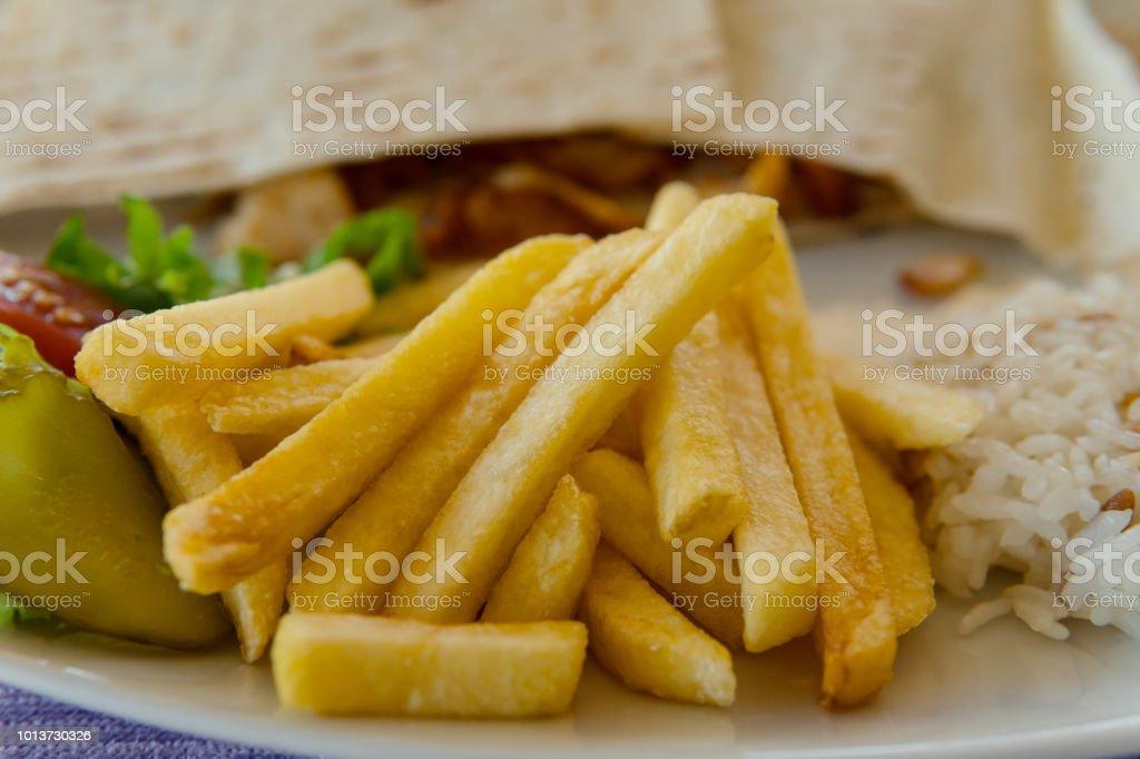 Nahaufnahme von Pommes frites, Reis und Döner auf Teller – Foto