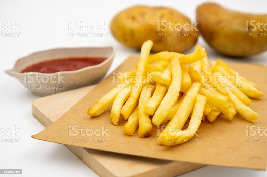 Close up of French fries with ketchup and raw potatoes on a white background. zbiór zdjęć royalty-free