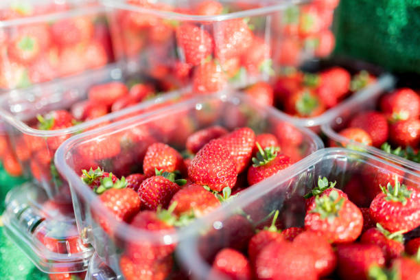 Close up of fresh and ripe English summer strawberries in punnets on a market stall in the Yorkshire in the UK Close up of fresh and ripe English summer strawberries in punnets on a market stall in the Yorkhsire, England in the UK fruit carton stock pictures, royalty-free photos & images