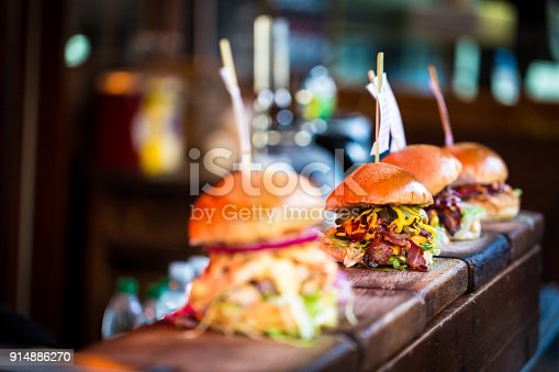 Close up image of a selection of freshly flame grilled burgers in a row on a wooden counter at Borough Market, one of the oldest and most famous food markets in the world. Each of the burgers has its own label, on which is written the contents of the burger. The burgers are sandwiched between glazed buns, and presented on beds of fresh green lettuce and stuffed with melted cheese and red onion. Horizontal colour image with copy space.