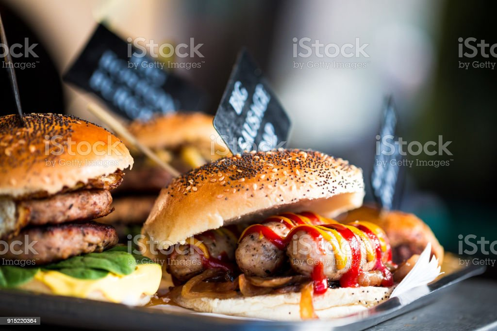 Close up of fresh flame grilled burgers with sausages displayed in a row at food market