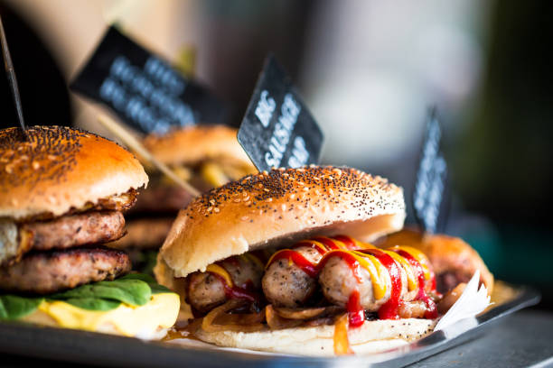 Close up of fresh flame grilled burgers with sausages displayed in a row at food market stock photo