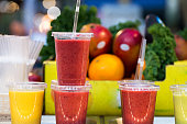 Close up color image depicting freshly made fruit juices and smoothies on display in a row and for sale at Spitalfields Market, a food and vintage market in east London, UK. In the background, defocused, is a pile of fresh fruit and vegetables - the raw ingredients used to make the smoothies. Room for copy space.