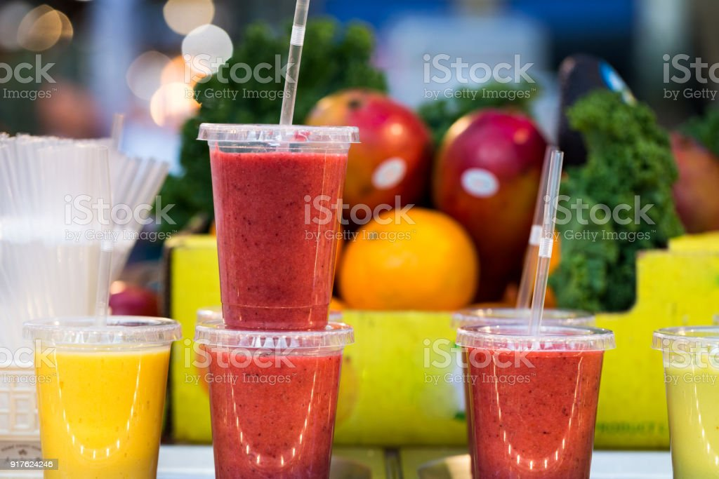 Close up of fresh fruit smoothies and juices in a row for sale on vegetarian market stall stock photo