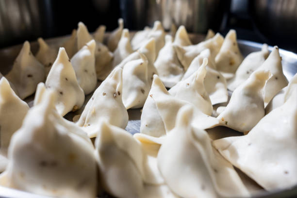 close up of fresh homemade samosas in kitchen in preparation, samosas are a staple of indian diet and a classic street food stock photo