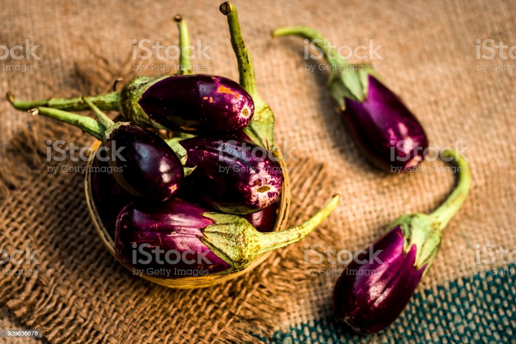 Close up of fresh raw egg plant,Solanum melongena or Brinjal in a traditional basket on gunny background. stock photo