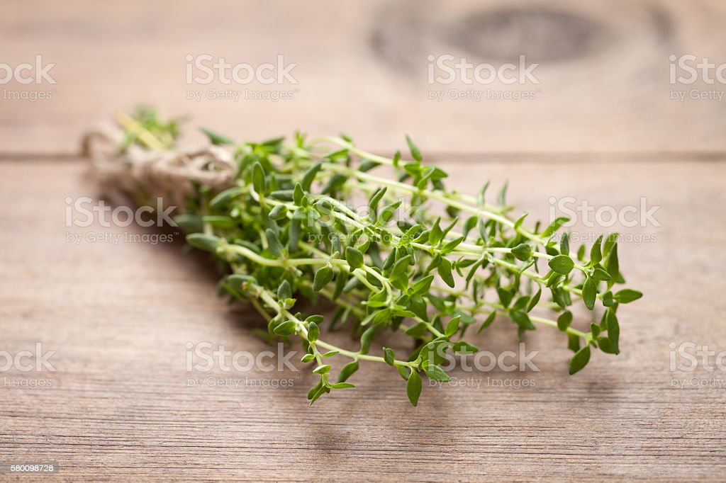 Close up of fresh thyme on old wooden table stock photo