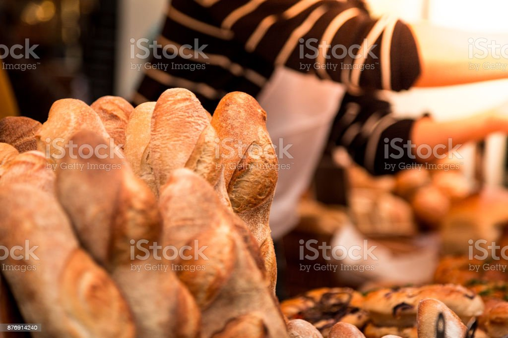 Close up of freshly baked artisan baguettes in a row with baker in background stock photo