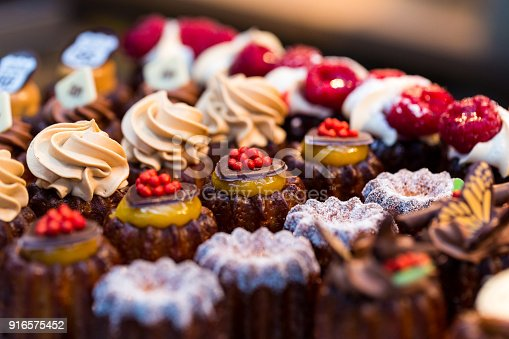 Close up horizontal color image depicting a selection of freshly baked delicious cakes and cupcakes for sale at Borough Market in London, one of the oldest and most popular food markets in the world. The gourmet cakes are topped with all kinds of things, including whipped cream and fresh strawberries. Room for copy space.