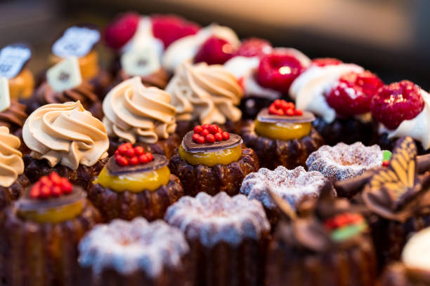 close up of freshly baked cakes and cupcakes in a row at food market - panetteria foto e immagini stock