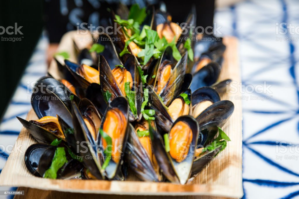 Close up of freshly cooked mussels in shells presented in wooden bowl at food market, Borough Market, London, UK stock photo