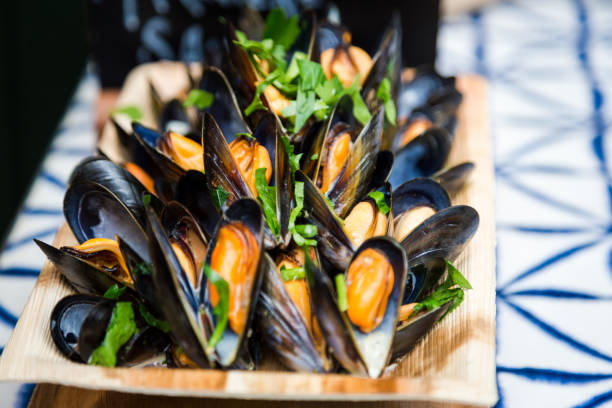 Close up of freshly cooked mussels in shells presented in wooden bowl at food market, Borough Market, London, UK Color image depicting freshly cooked mussels in their shells, presented in a rustic wooden bowl at Borough Market, one of the most popular food markets in London and in the world. Close up image with room for copy space. mollusk stock pictures, royalty-free photos & images