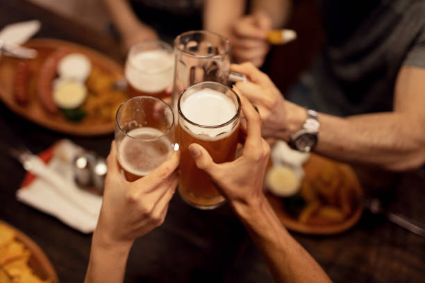 close up of friends toasting with beer and having fun in a pub. - bar foto e immagini stock