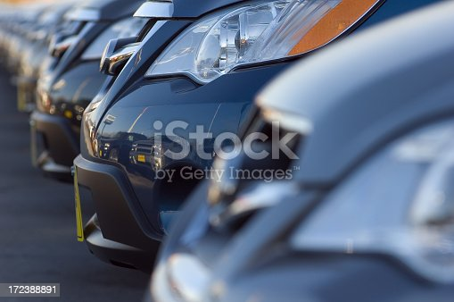 Row of brand new cars at a car dealership. Focus is on the headlight of a second car.