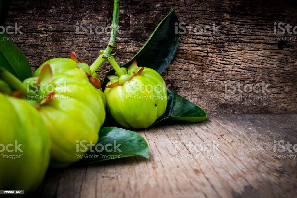Close Up Of Garcinia Cambogia Fresh Fruit On Wood Background Stock