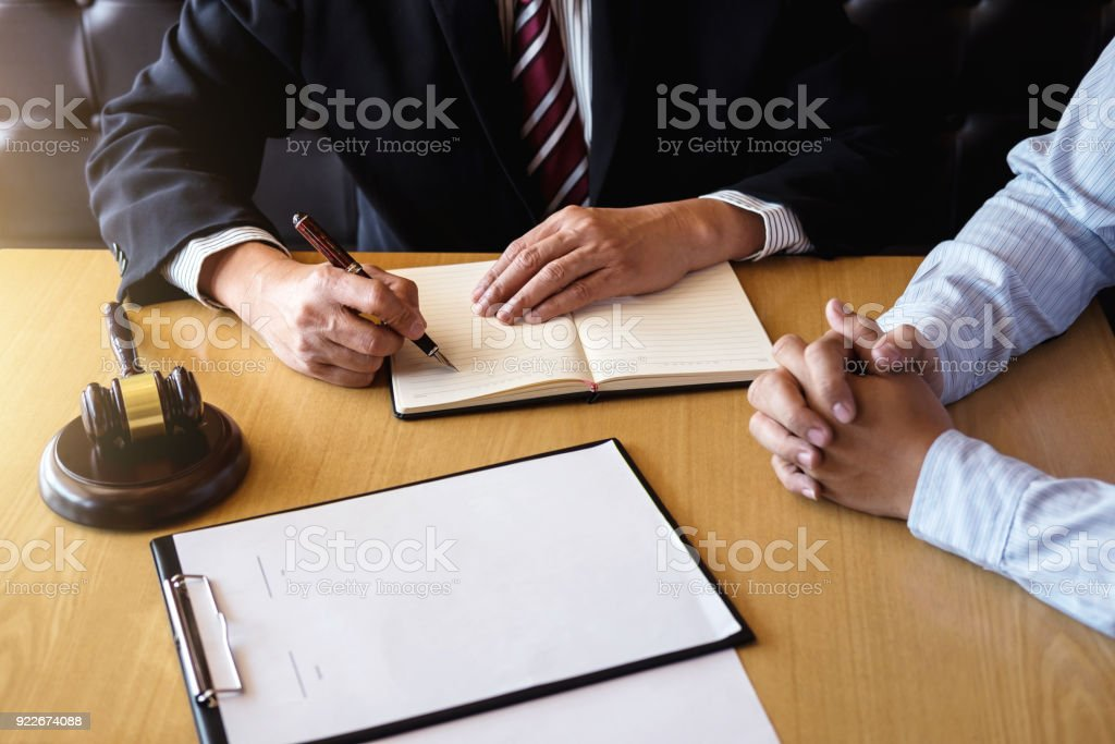 Close up of gavel, Male lawyer or judge Consult with client and working with Law books, report the case on table in modern office, Law and justice concept stock photo