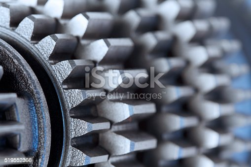 A steel blue cast dominates a stack of industrial gears photographed with a shallow depth of field.