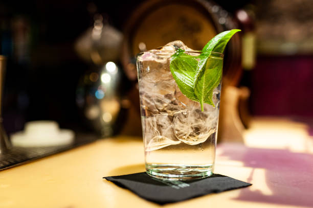 close up of gin tonic glass inside bar on top of bar counter with ice cubes and basil leaves at night stock photo
