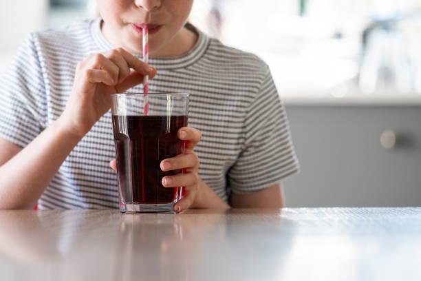 close up of girl trinken sugary fizzy soda aus glas mit stroh - alkoholfreies getränk stock-fotos und bilder