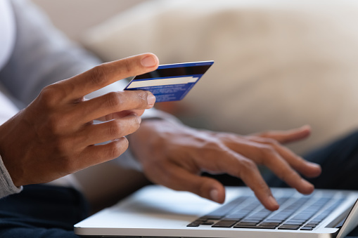 Close up of black girl hold bank credit card and type on laptop, shopping online using computer, buying goods or ordering online, entering bank accounts and details in online banking offer