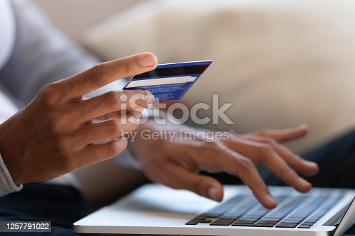 istock Close up of girl hold bank card and type on laptop 1257791022