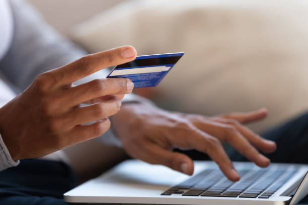Close up of girl hold bank card and type on laptop stock photo
