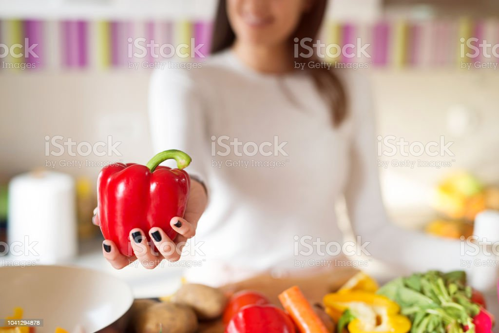 Close up of girl holding red paprika in her hands. Focus is on paprika. stock photo