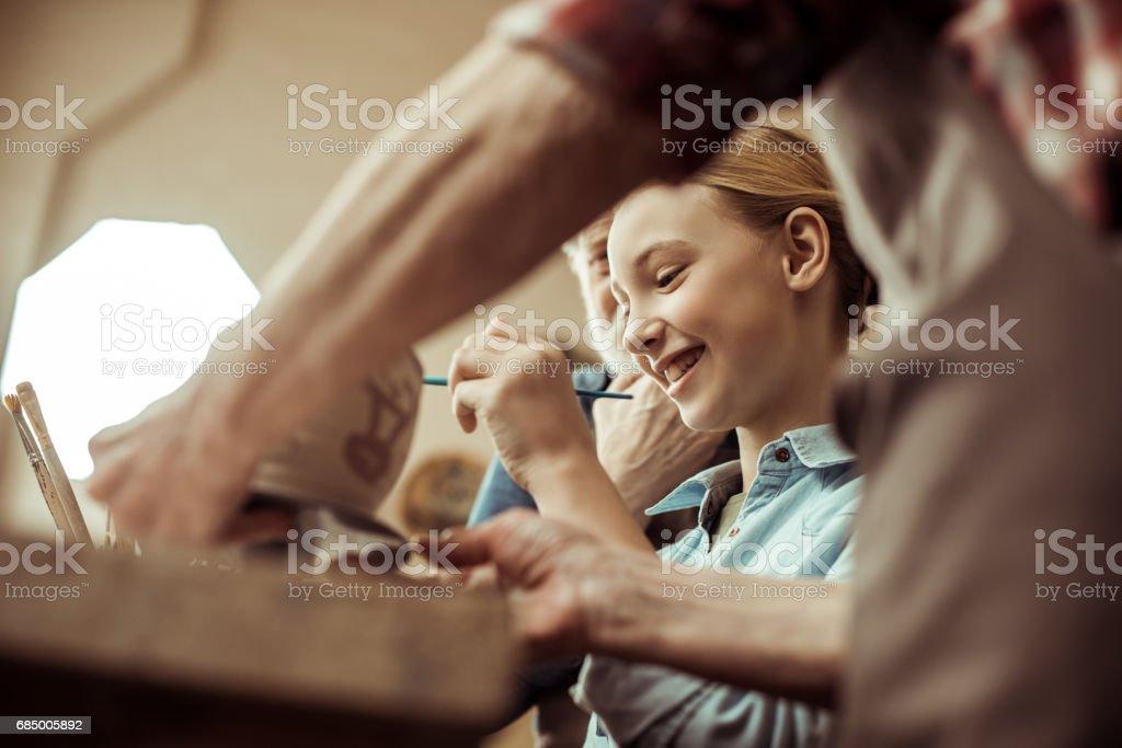 Nahaufnahme von Mädchen Malerei Tontopf und Großeltern helfen beim workshop Lizenzfreies stock-foto