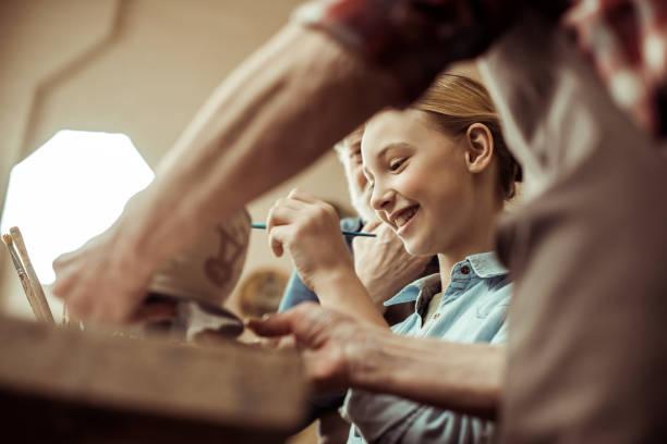 nahaufnahme von mädchen malerei tontopf und großeltern helfen beim workshop - handbemalte teller stock-fotos und bilder