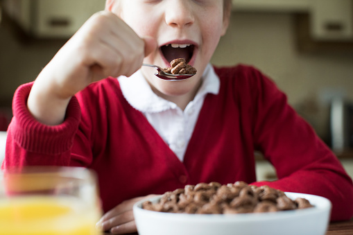 Close Up Of Girl Wearing School Uniform Eating Bowl Of Sugary Breakfast Cereal In Kitchen Stock Photo - Download Image Now