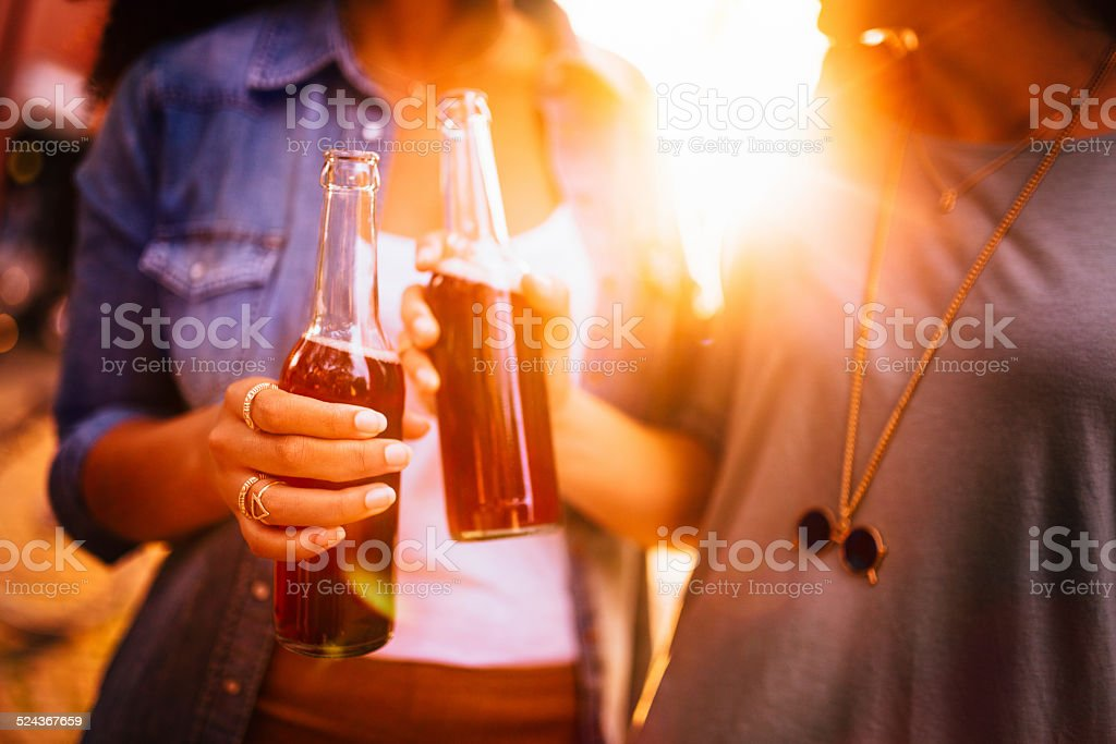 Close Up Of Girls Enjoying Pink Lemonade Together Outside stock photo