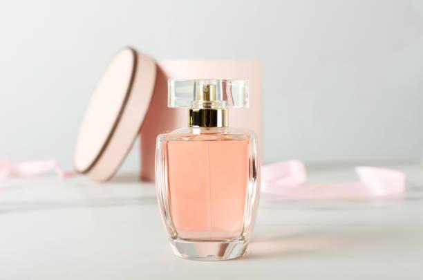 zbliżenie szklanej butelki perfum i otwarte pudełko jako tło na białej powierzchni - perfumowany zdjęcia i obrazy z banku zdjęć