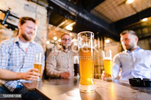 istock Close up of glass full of beer. Tree male friends sitting in a bar and drinking beer. 1043561006