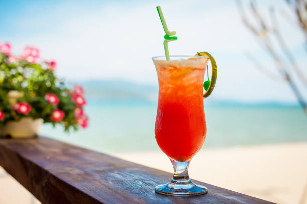Close up of glass with refreshing orange cocktail with cherry on table on beach. - foto stock