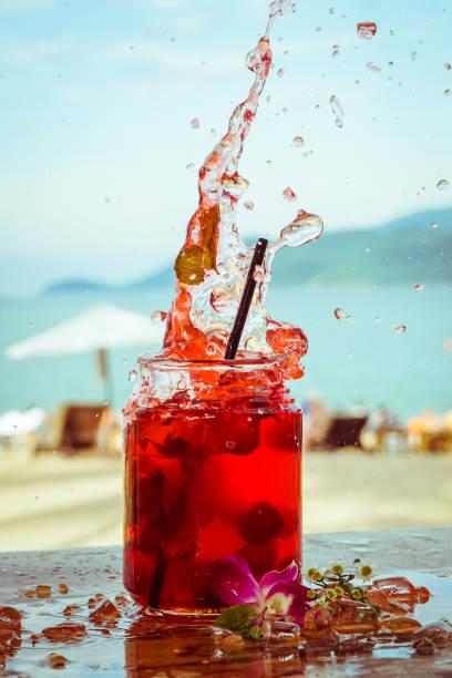 närbild av glas med uppfriskande strawberry cocktail med lime, mynta med stänk på beach bar bakgrund - cactus lime bildbanksfoton och bilder